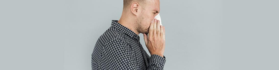 uomo che si soffia il naso